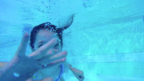Underwater shot of two kids diving in a swimming pool stock video