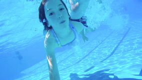 Underwater shot of two kids diving in a swimming pool. Slow motion Underwater shot of two kids diving in a swimming pool stock video