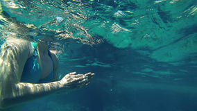 Underwater shot of woman swimming in sea stock footage
