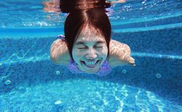Underwater shot of young woman diving into the swimming pool.  royalty free stock image