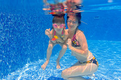Underwater smiling family diving in swimming pool. Happy mother and kid swim, diving, playing and having fun underwater. Summer vacation Royalty Free Stock Photo