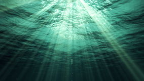 Underwater Sun Rays in the Ocean (Loop). Underwater view with ripples coming towards camera. Sun rays shinning down. Seamless looping video animation stock footage