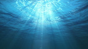 Underwater Sun Rays in the Ocean (Loop). Underwater view with ripples coming towards camera. Sun rays shinning down. Seamless looping video animation stock video footage