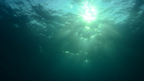 Underwater sunburst. Effects odf the light coming from the sun under the water´s surface stock video