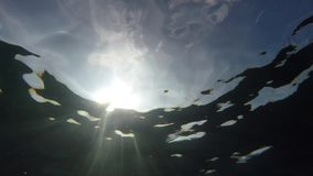 Underwater sunrays shine. Into the water stock video