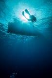 Underwater sunshine below the boat in Derawan, Kalimantan, Indonesia underwater photo. Diver swim heading to the boat Stock Photos