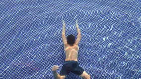 Underwater Swimmer. A boy swimming across the pool underwater stock footage