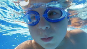 Underwater swimming of a child in goggles. Slow motion close-up shot of a boy in goggles diving and swimming underwater in the pool by vacation home stock footage