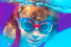 Underwater swimming girl goggles blue water royalty free stock photo