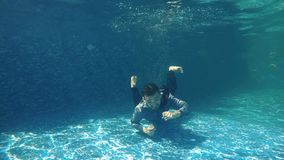 Underwater swimming in swimming pool. Underwater. Businessman in suit dives under water in blue swimming pool. The guy in suit creates air bubbles around him and stock video