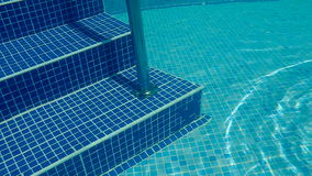 Underwater swimming pool staircase. A blue water pool steps with metal grab bars stock video