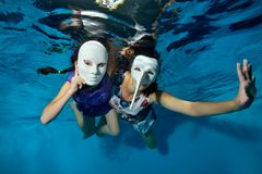 Underwater theater. Two unusual girls swim and play underwater in the pool on a blue background in white masquerade masks. In beautiful dresses and look at the royalty free stock images