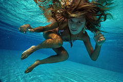 Underwater View. Attractive young woman floating in beautiful ethereal swimming pool Stock Photo