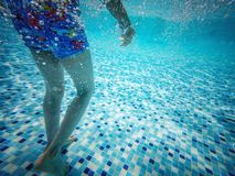 Underwater view of child in swimming pool. A underwater view of the legs of a child in a swimming pool on holiday royalty free stock image