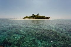 Beautiful turquoise coral reefs surrounding small tropical island Royalty Free Stock Photos