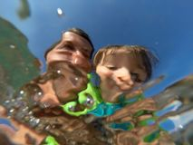 Underwater view of a father and her daughter with distorted face. Father and her toddler daughter having fun at the sea. Distorted faces view through water Stock Photo