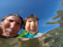 Underwater view of a father and her daughter with distorted face Stock Photography