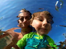 Underwater view of a father and her daughter with distorted face Stock Photo