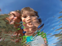 Underwater view of a father and her daughter with distorted face Royalty Free Stock Images