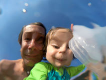 Underwater view of a father and her daughter with distorted face Royalty Free Stock Photography