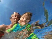 Underwater view of a father and her daughter with distorted face Royalty Free Stock Photo