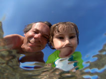 Underwater view of a father and her daughter with distorted face Stock Image