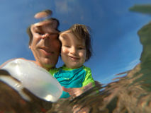 Underwater view of a father and her daughter with distorted face Royalty Free Stock Image