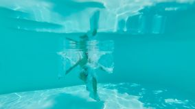 Underwater View Of Man Jumping In A Pool. Underwater view of man jumping in a blue swimming pool Royalty Free Stock Photos