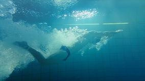 Underwater view of man swimming and diving. In the pool stock video
