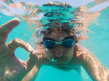Underwater view of a man swimming in the sea. Underwater view of man swimming in the sea Royalty Free Stock Images