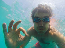 Underwater view of a man swimming in the sea. Underwater view of man swimming in the sea Royalty Free Stock Photo
