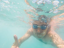 Underwater view of a man swimming in the sea. Underwater view of man swimming in the sea Royalty Free Stock Image
