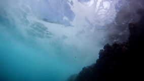 Underwater View of an Ocean Wave Passing Over. Swimming underwater in the ocean as a wave passes above, then surfacing near rocks stock video