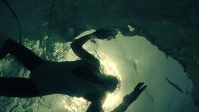 Underwater shot of a slim young woman in a swimsuit bathing in the sea. Underwater view straight up to a girl bathing in the sea stock video footage