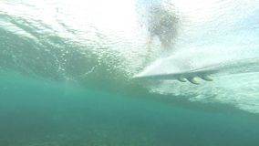 Underwater view of surfer riding wave Royalty Free Stock Image