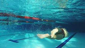 Underwater view swimmer swiming crawl stroke in the pool. Underwater view to the professional swimmer swiming crawl stroke in the pool, reaching the wall stock footage