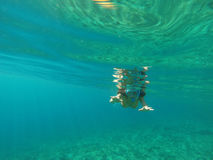 Underwater view of a woman snorkeling in the tropical sea Stock Photo