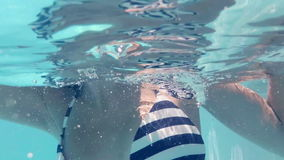 Underwater view of woman swimming in the pool stock video footage