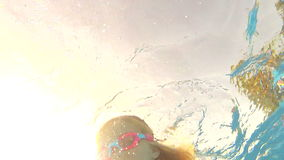 Underwater view young girl wearing. Goggles swims towards and over camera.Shot on Canon 5D Mk2 at at a frame rate of 30 fps stock footage