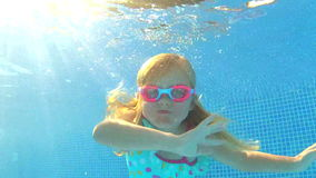 Underwater view young girl wearing. Goggles waving at camera.Shot on Canon 5D Mk2 at at a frame rate of 30 fps stock video footage