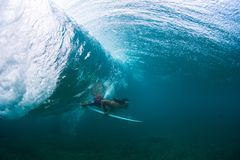 Underwater view of the young male surfer. Passing the ocean wave with surf board Stock Photo