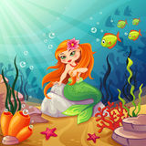Underwater worlds with a mermaid on the rock Royalty Free Stock Image