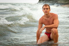 Underwear Model on Beach. Attractive man in underwear on a beach at sunrise Royalty Free Stock Image