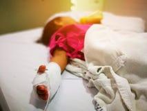 Undeutliche Kinder sind der schlafende Kranke und benutzen Salzlösung am Krankenhaus, Klimawandelursachen die Grippe Stockfotos