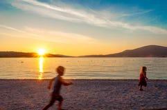 Undeutliche kleine Kinder, die auf Strand bei Sonnenuntergang laufen Stockfotografie