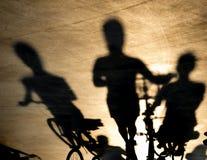 Undeutlicher Schatten von drei jungen Frauen auf Fahrrädern stockbilder