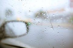 Undeutlicher Tropfen des Regens auf Autoseitenspiegel auf der Straße mit Weinlese Stockfotos
