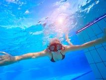 Undewater заплывания молодой женщины в бассейне стоковое фото