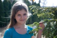 Undici anni di ragazza con l'albero di abete all'aperto Fotografia Stock Libera da Diritti