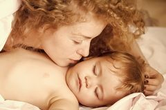 Undisturbed sleep of the child. Mother with baby. Undisturbed sleep of the child. Closeup of young loving mother with light blonde curly hair sleeping with royalty free stock photography